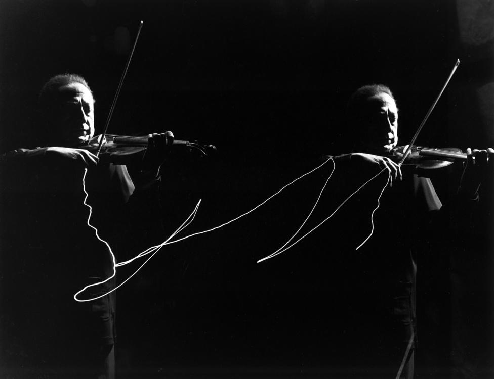 Hogyan fényképeznéd le a zenét? Mili ezt is megoldotta: Jashca Heifetz hegedűs vonójára szerelte a kis fényforrást, így tudta megörökíteni a vonó mozgását, miközben egy szép dupla portré is készült a hegedűművészről.