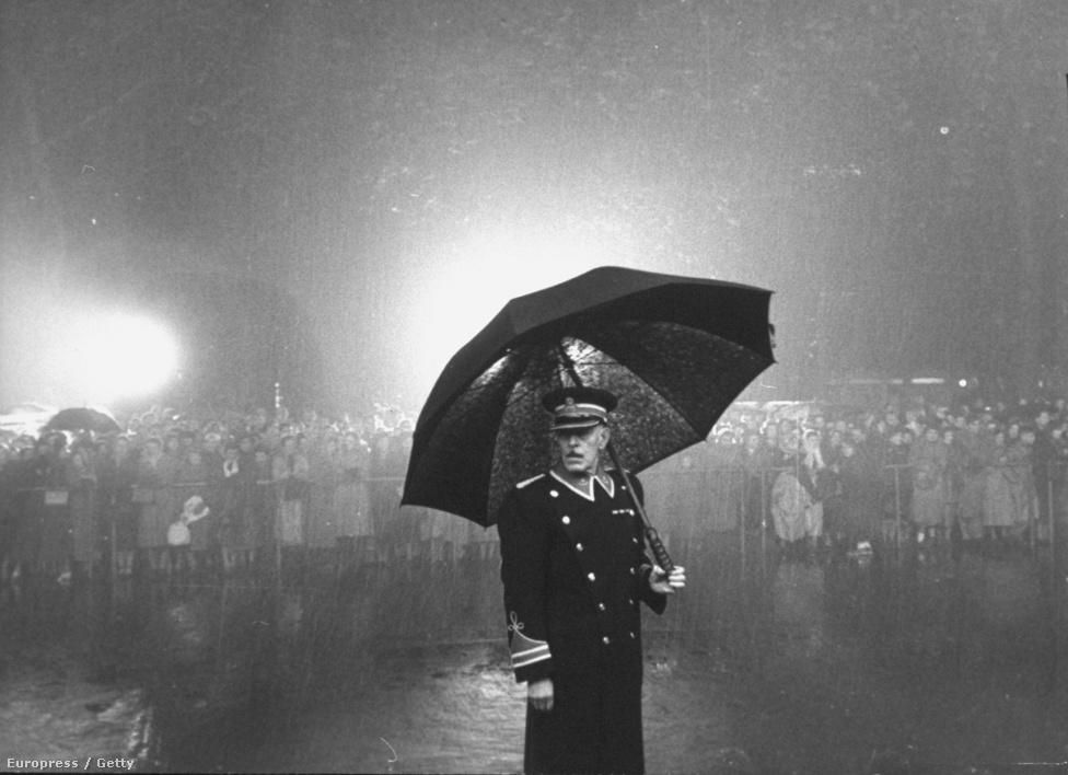 Az ilyen képek láttán mindig jusson eszünkbe, hogy Cornell Capa nem tartotta magát jó fotósnak. Angolok és szokásaik 1950-ben: az ajtónálló egy hatalmas esernyővel áll az esőben.