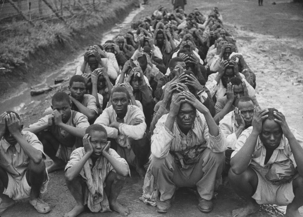 1954, Kenya. Afrikába költözése után Spencer lett a kontinens fotósa, minden fontos eseményt, harcot ő örökített meg. A képen a britek által bebörtönzott Mau Mau felkelők, a felkelés végéig a polgárőrség 4686 Mau Maut ölt meg
