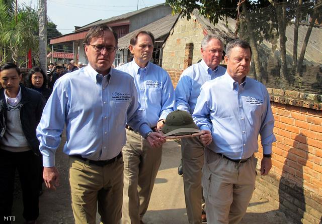 A vietnami háborúban elesett észak-vietnami katona Bui Duc Hung rohamsisakját viszi John Abbey Daniel Gregg Mike Breuker és Fred Grimm amerikai veterán (b-j) az északi Phu Tho tartományban fekvő Huong Non faluban 2014. január 14-én.