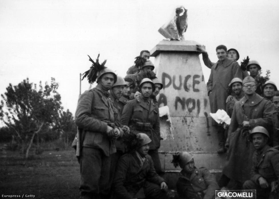 """Donyecknél, az orosz fronton olasz katonák pózolnak 1941-ben Lenin ledöntött szobra előtt, aminek a talapzatára az """"Éljen a Duce!"""" fasiszta szlogent festették."""