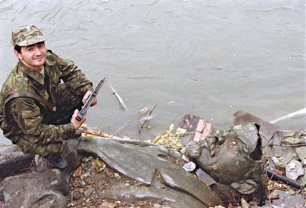 Csecsen fegyveres egy betört fejű Lenin-                         szobor tetején 1991. október 25-én, a Groznijhoz közeli Sonja folyónál. A szobor szépen lassan megindult az enyészet útján.