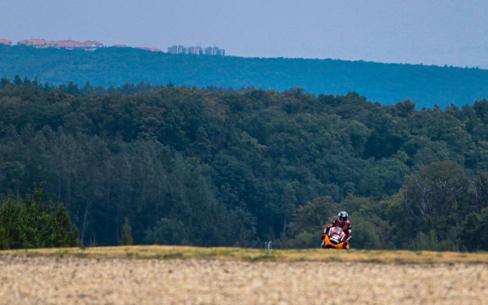 Colin Edwards, a MotoGP edzésén érkezik az erdő sűrűjéből. Távolban a város szélén húzódó házak.