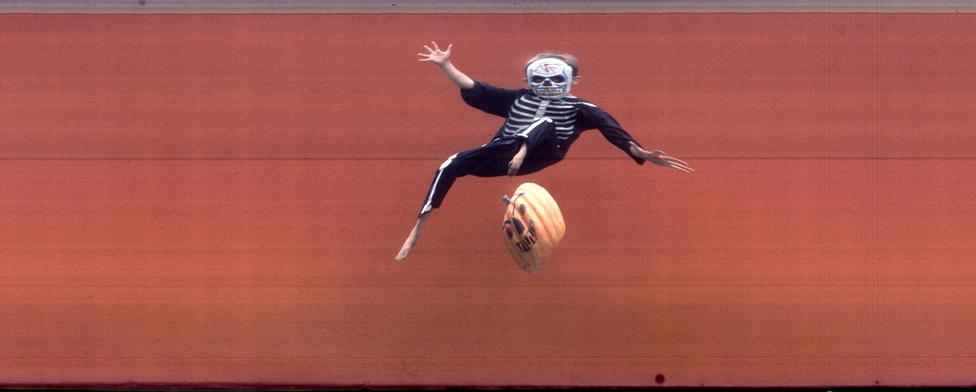 Silk akkor fedezte fel a célfotó kamerával készült képekben rejlő lehetőségeket, amikor az 1959-es Kentucky Derbyről tudósított. Az alakok furán jelennek meg , hiszen csak egy csíkban fotózott a kamera. így a mozgó alakok speciális nyúlt formát kapnak. Silk egy hordozható változatot csináltatott magának, ezt próbálta ki 1960 Halloweenjén a saját gyerekén. Akinek természetesen, mint annyi Silk-fotó szereplőjének, a lába nem érte a földet.