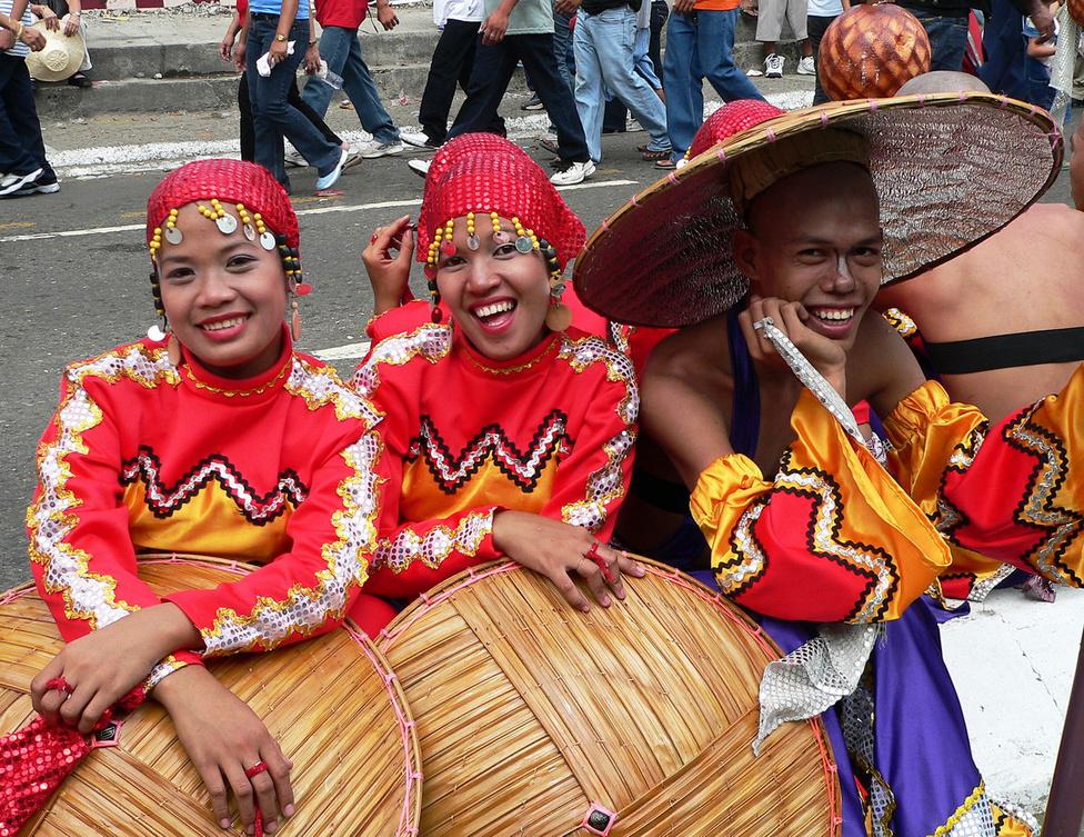 Parádéra várva a Sinulogon. Mivel a népszaporulat nagy, a Fülöp-szigeteken magas a fiatalok aránya. Ráadásul a lányok gyönyörűek! Mivel sok a szegény család, már évtizedek óta virágzó üzlet a feleségközvetítés. Számtalan ügynökség közvetít a fejlett országokba fiatal nőket, akik ily módon révbe érve rendszeresen segítik anyagilag az otthon maradottakat. E sorok íróját szó szerint berángatta egy nagyon kedves család a házába. Leültették az emeleti nagy teraszon, üdítővel kínálták, és a családfő előrántott egy fotóalbumot az eladó lányáról, javasolva, hogy máris kössük meg az egyezséget. Marasztaltak, hogy ne siessek, a reménybeli ara nemsokára megjön a gimnáziumból, de szerintük felesleges sokat morfondírozni, addig megbeszélhetjük a részleteket is. Elfogyott még két kóla, mire sikerült meggyőzni a szülőket, hogy ez a gyönyörű trópusi virág elhervadna a hideg európai levegőn.