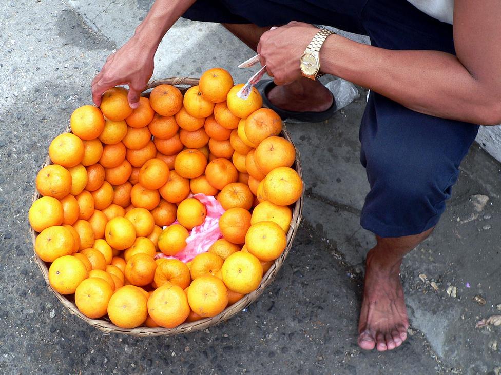 Narancsárus Cebuban. A friss és ízletes, helyben termelt gyümölcsöt nem kilóra mérik az utcán, hanem darabonként árulják. Sokan csak egyet vesznek, és frissítőként gyorsan be is dobják. Az árus az ujjai közé simított papírpénzzel azt szuggerálja a vevőknek, hogy lám, már vásároltak tőle, tehát az áruja ízletes. A szegénység az oka, hogy nemcsak gyümölcsöt árulnak és vesznek ilyen kis tételben, hanem például cigarettát is lehet szálanként vásárolni.