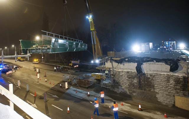 A Szentendrei út felett átvezető vasúti híd 57 tonnás elemét emelik a helyére daruval Budapesten a Pók utcánál 2013. december 14-ére virradó éjjel.