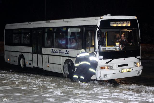 Tűzoltók tolják ki az árokból a Balaton Volán autóbuszát amely az ónos eső miatt megcsúszott a szentkirályszabadjai buszfordulónál
