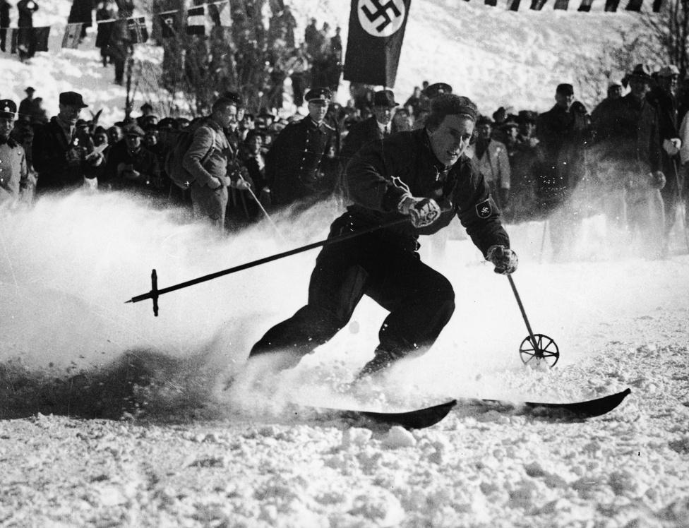 Kezdetben a Nemzetközi Olimpiai Bizottság törekvése az volt, hogy ugyanaz az ország rendezze a téli és a nyári olimpiát is. 1936-ban ez azonban nem sült el túl jól, Hitler mindkét eseményt, a berlini és a garmisch-partenkircheni olimpiát a náci propaganda céljaira használta fel. A horogkeresztes zászló előtt a tizenkétszeres világbajnok Christl Cranz síel el. Cranz 1936-ben a kombináció világbajnoka lett.