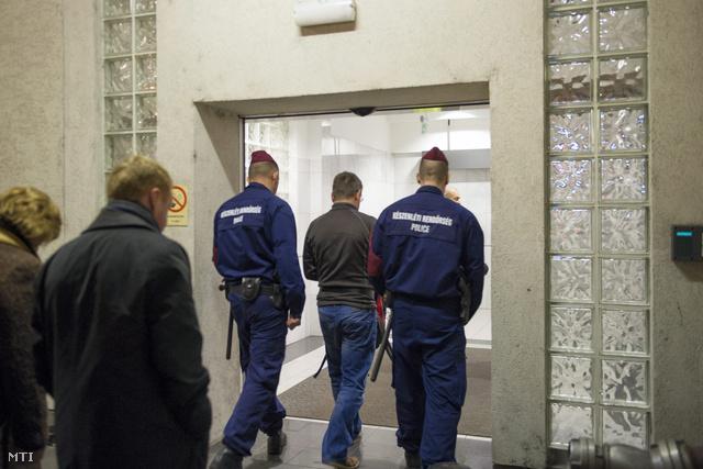 Francis Ciarán Tobint (k) kísérik rendőrök Budapesten a Liszt Ferenc-repülőtéren 2014. január 17-én.