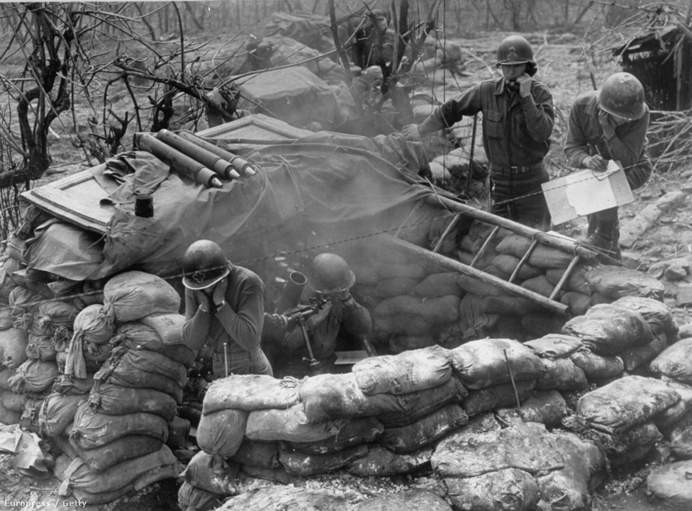 Amerikaiak fülüket befogva lövik a rakétákat, míg egy társuk telefonon kapja az utasításokat és a német csapatok pozíciójáról szóló információkat. Az olasz front, 1945-ben.