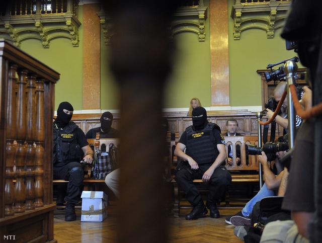 P. Tamás elsőrendű vádlott (az oszlop takarásában) a Prisztás-gyilkosság tárgyalásán a Fővárosi Törvényszéken 2013. május 17-én.