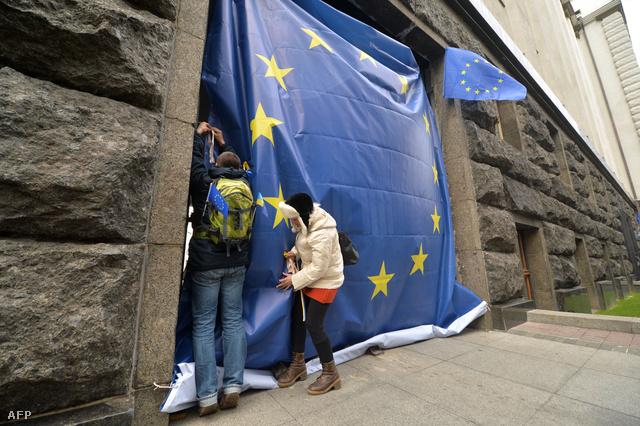 Ukrán tüntetők igazgatnak egy zászlót a Belügyminisztérium épületének bejáratánál