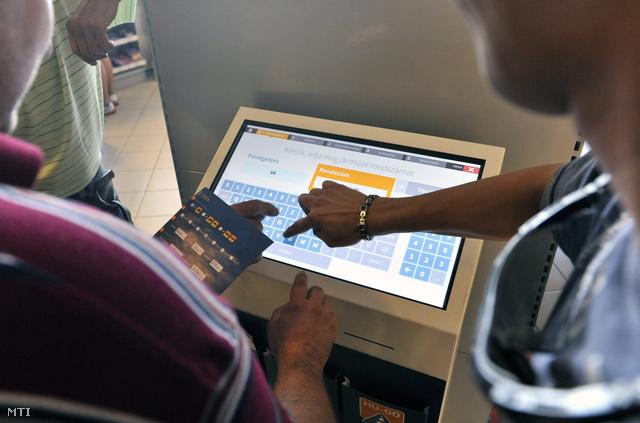 Kamionsofőrök viszonylati jegyet vesznek az e-útdíj megfizetésére Budapesten az Ócsai út egyik benzinkútjánál lévő terminálnál 2013. július 1-jén.