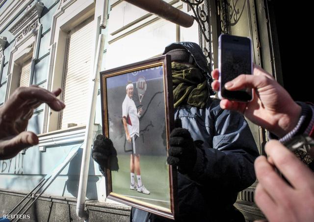 Janukovics portréja egy tüntető kezében a pártszékház előtt