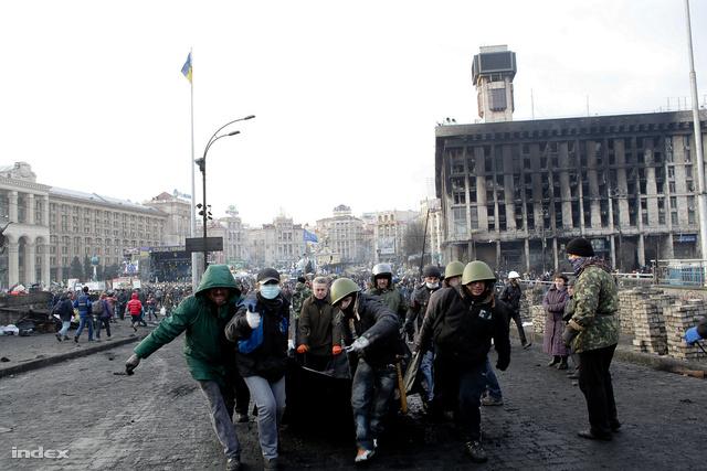Anyagot visznek a barikádokhoz. A háttérben a Szakszervezetek Házának kedd éjszaka kiégett épülete áll.