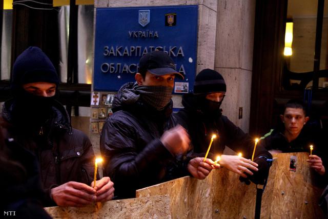 Aktivisták imádkoznak a Kijevben elhunyt forradalmárok emlékére a Kárpátaljai megyei állami közigazgatási hivatal előtt tartott gyászmisén Ungváron 2014. február 20-án este.