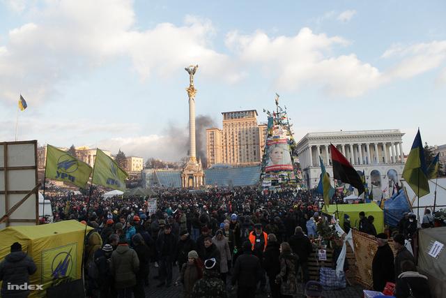 A tüntetések központjában, a Maidanon több százezer ember táborozik hónapok óta. A képekkel teleaggatott gúla eredetileg egy karácsonyfa lett volna. Decemberben ennek felállítása ürügyén már meg akarta tisztítani a tüntetőktől a teret a hatalom, már akkor sem sikerült. Helyette most Janukovics legfőbb ellenfele, a börtönben ülő Julija Timosenko portréját és kormányellenes molinókat tart a magasba.