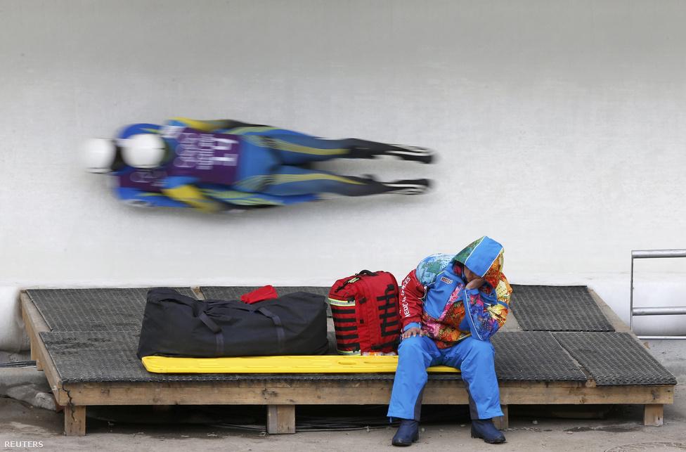 Egy pályamunkás pihen a 100 km/h-nál is nagyobb sebességgel száguldó ukrán szánkósok mellett. A szánkóverseny nem róluk, hanem a németekről szólt, akik mind a négy olimpiai aranyat megnyerték, ezzel pedig történelmet írtak, hiszen a váltóversenyt 2014-ben rendezték meg először.