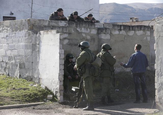 Ukrán katonák (fent) és feltehetően orosz katonák beszélgetnek egy ukrán katonai létesítmény kerítésénél Szimferopolban
