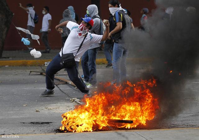 Egy kormányellenes tüntető követ dob a rendfenntartókra.