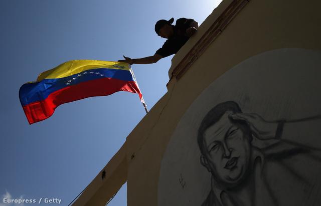 """Chávez egyik híve zászlót tűz egy a volt elnök képével díszített falra, a """"Comandante Supremo"""" sírja közelében."""