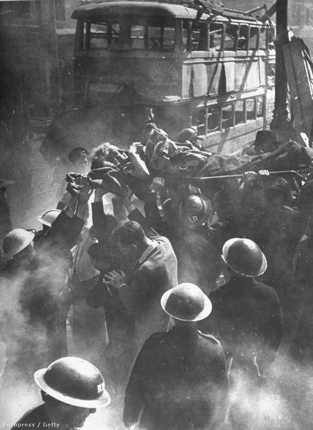 A német bombázásokban megsebesült angol nőt szállítanak a fejük fölé emelt hordágyon.