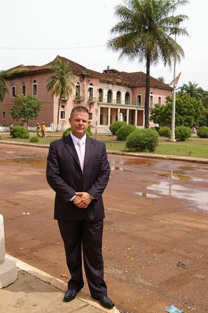 Welsz Tamás pózol azelőtt a Bissau-guineai épület előtt, ahova Simon Gábor volt bejelentve