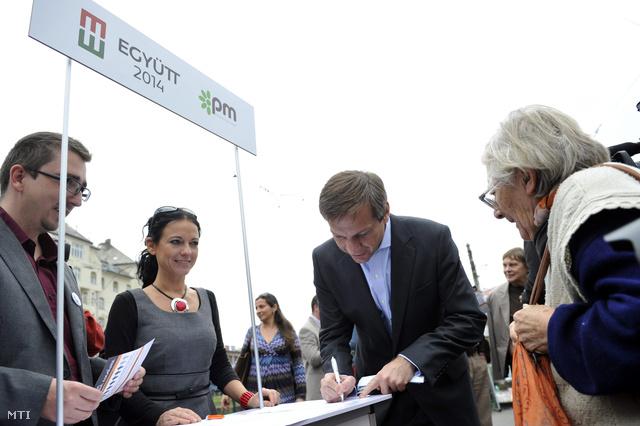 Bajnai Gordon az Együtt-PM szövetség vezetője aláírja az egyik aláírásgyűjtő ívet a Széll Kálmán téren 2013. október 28-án.