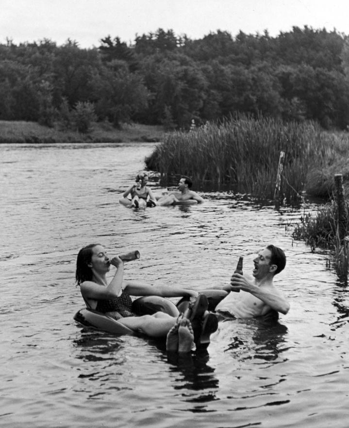 1941. Ezzel képpel egészen nyudodtan lehetne sört is reklámozni, annyira tökéletesen visszaadja egy forró nyári nap léhaságát és egy hideg sör élményét. A fotó 1941-ben készült, a gumibelsőben söröző pár az Apple-folyón sütteti a hasát.