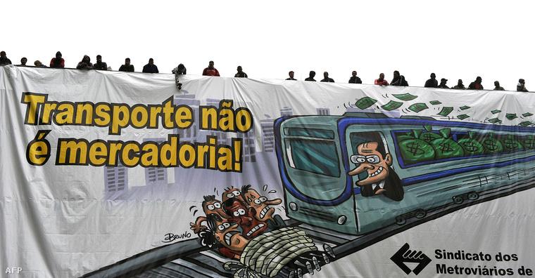 Sao Paulo állam kormányzója, Geraldo Alckmin vezeti a pénzzel tömött metrókocsit a korrupció ellen tüntetők által kifeszített transzparensen