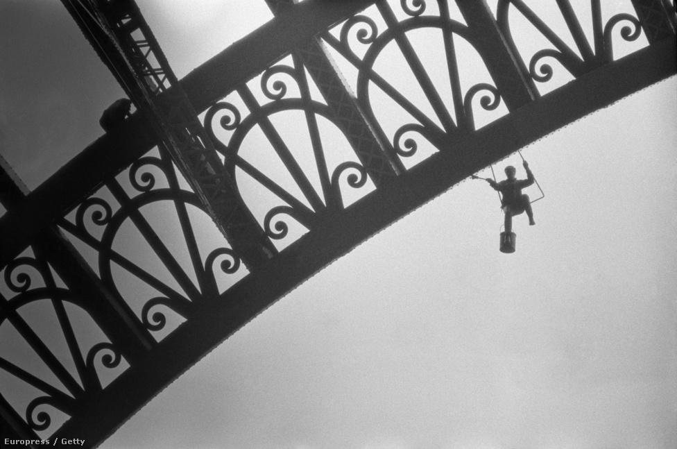 Egy női munkás festi az Eiffel-tornyot. 1969-es felvétel.