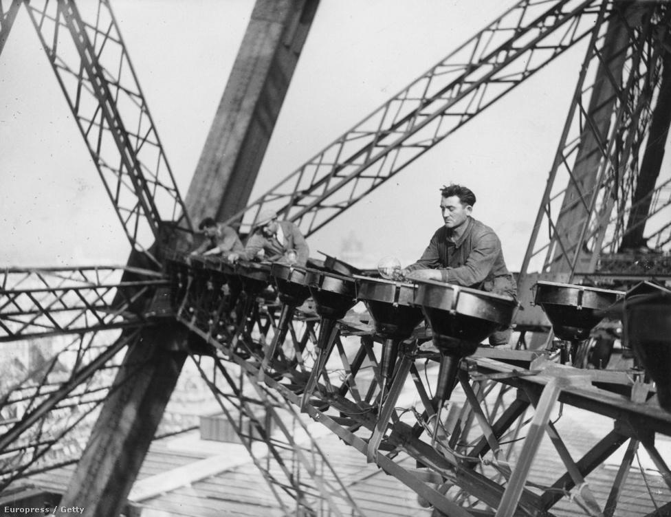A villanyszerelők kicserélik az Eiffel-tornyot éjjel megvilágító lámpák égőit. A fotó 1937. október 29-én készült.