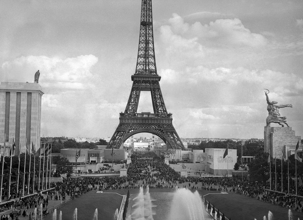 Egy kép, ahol nem a középen látható Eiffel-torony a fő attrakció, hanem a két oldalsó épület. A fotó az 1937-es Exposition Internationale des Arts et Techniques dans la Vie Moderne kiállításon készült. Balra látható Albert Speer német építész munkája: a szögletes épület, a tetején a birodalmi sassal, előtte a horogkeresztes zászlóval. Jobbra Borisz Iofan szocialista építész műve látható, a tetején Vera Mukina szobrával; ez egy munkást és egy parasztasszonyt ábrázol, amint a levegőbe emelik a sarlót és a kalapácsot.