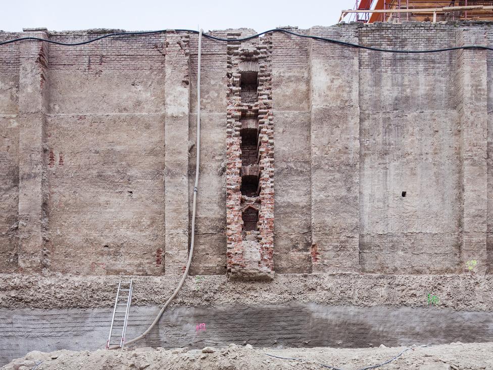 Kibontott fal a rámpák mögött.  A falban látható üregsor egy korabeli vízelvezető maradványa. Alulra mélygarázsok, fölé egy multifunkciós terem kerül. Ennek tetejére ismét kertet telepítenek vissza.