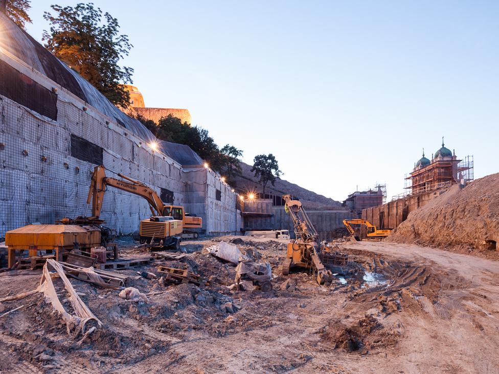 Balra a Vár, szemben a Déli kortinafal a Vízhordó lépcsővel, jobbra a gloriette, a Várbazár központi eleme, melyhez rámpák vezetnek fel. A képen látható helyen egykor már a Várhegy oldala volt, tetején a gyönyörű, geometrikus stílusú neoreneszánsz kerttel, melynek növényei a háború utáni ásatásoknak estek áldozatul. Most az építés során kibontották a Várbazár mögül földet.