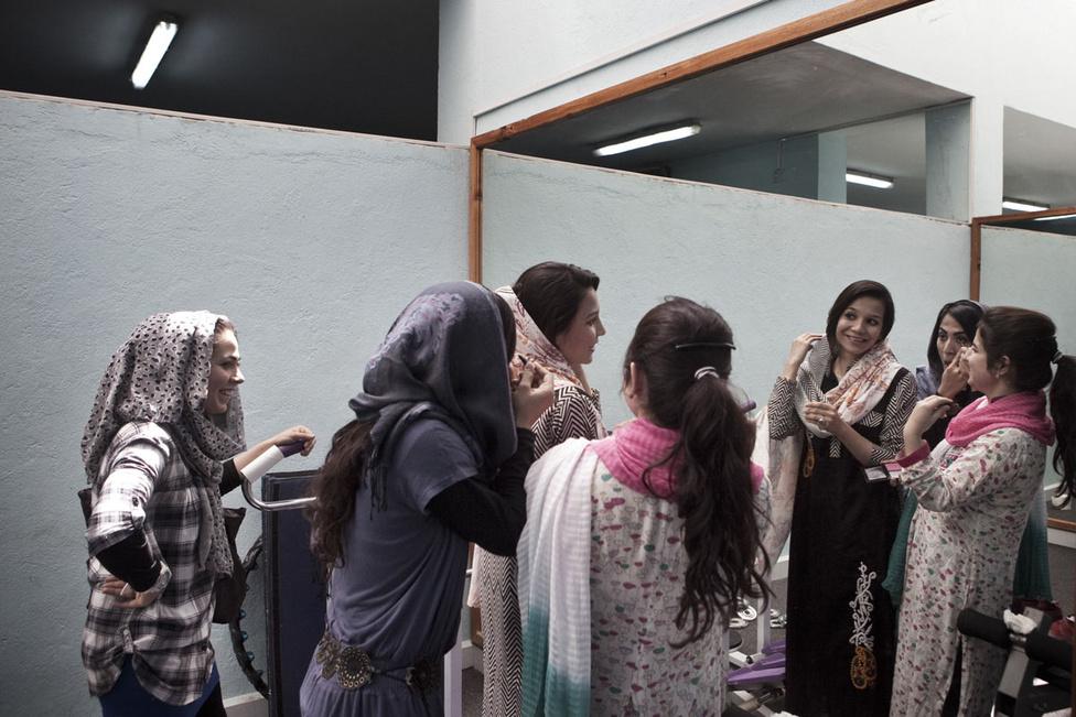 Egyetemista lányok sminkelnek az American University tornatermében. Bár az Egyesült Államokból kapott ösztöndíjuk a tandíj (nem kis összeg, akár évi 6000 dollár) nagyobb részét fedezi, ők így is csak a privilegizált elitbe tartozó családokat képviselik. Az öt hold kiterjedésű egyetemi kampusz külön sziget Kabulban.