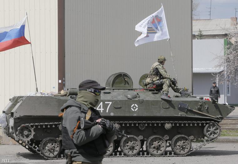 Csuklyás fegyveres oroszbarát szakadárok páncélozott járművel a kelet-ukrajnai Szlovjanszkban