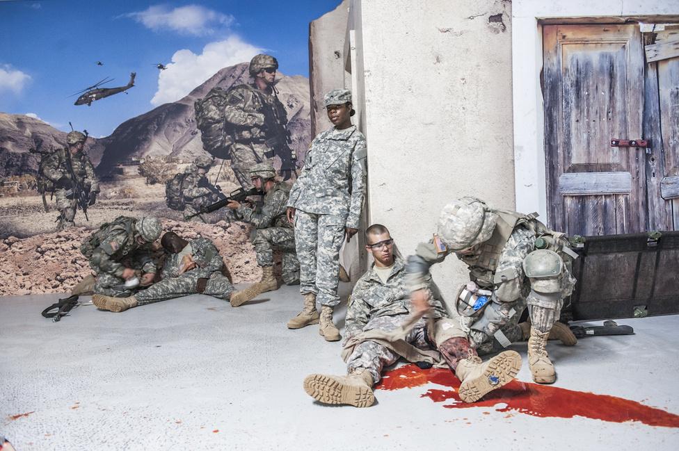 Harctéri elsősegély-képzés Fort Jacksonban, Dél-Karolinában. A sebesültek ordítanak, bár néhányan kínjukban el is mosolyodnak. A katonák feladata, hogy bekötözzék és biztonságos helyre vigyék a sérültet. Lassúak és ügyetlenek, de a képzők szerint gyakorlással fejlődni fognak.