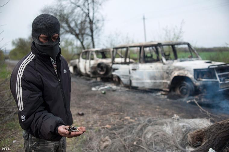 Töltényhüvelyeket mutat egy oroszbarát szakadár kiégett autóroncsok mellett Bilbaszivkában.