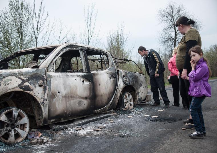Kiégett autóroncsot néznek meg helybeliek Bilbaszivkában.