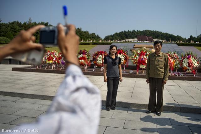 Észak koreai pár fotózkodik egy elesett katonáknak emelt síremléknél