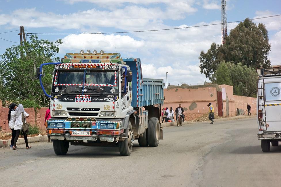 """Még sűrűbben lakott területekre érve előbukkantak a nagyobb teherautók, jellegzetes, harmadik világbeli díszítésektől rogyadozva. Kíváncsi vagyok, hogy Marokkóban van-e megfelelője annak a jelzőnek, amit a japánok az ilyen teherkocsikra használnak: """"deko-tora"""" (DECOrated TRUck)"""