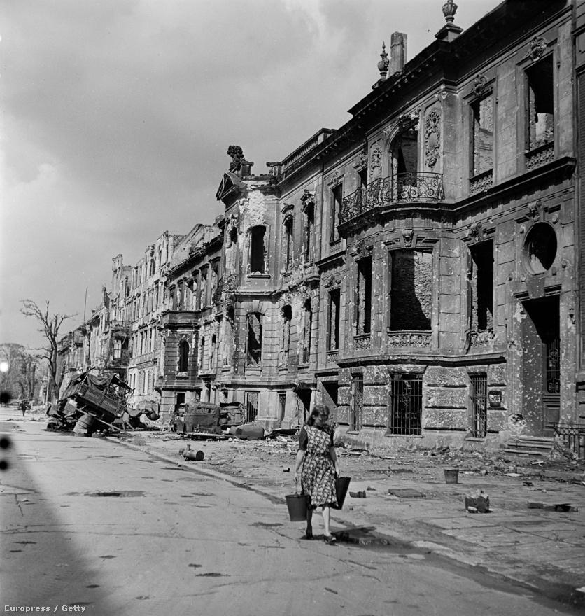 Vizet hord egy berlini lány a város egyik lerombolt utcáján.