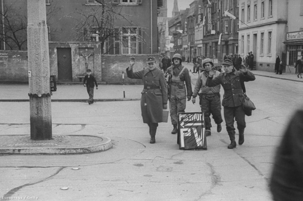 Két német hadifogolyt kísérnek amerikaiak egy háborús börtönbe Berlin utcáin.
