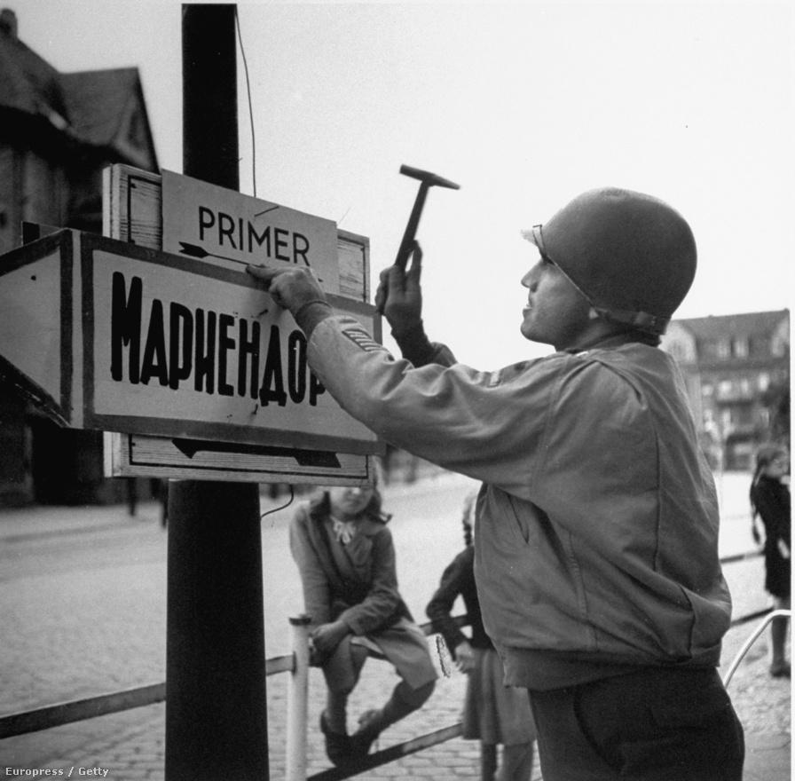 Amerikai katona szögel fel orosz és angol utcatáblákat egy póznára Berlinben.