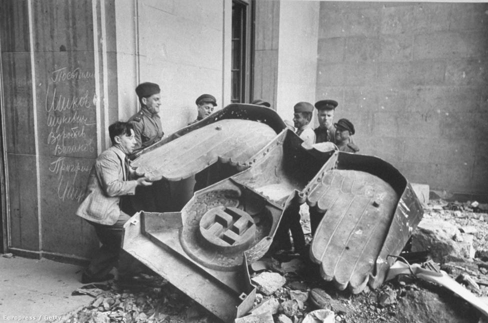 Orosz katonák cipelnek egy bronzból készült birodalmi sast, a náci párt jelképét, a Reichstag épülete előtt.