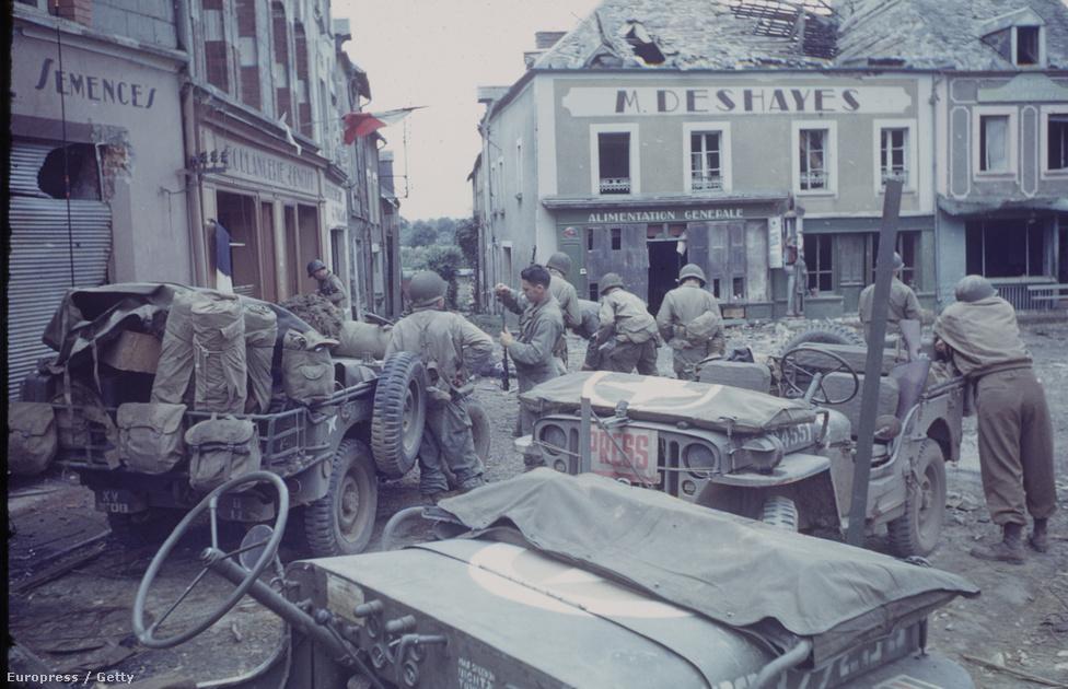 Amerikai csapatok és dzsipjeik – köztük egy sajtós jármű – Marigny városának főterén, Franciaország északnyugati partjainak közelében.