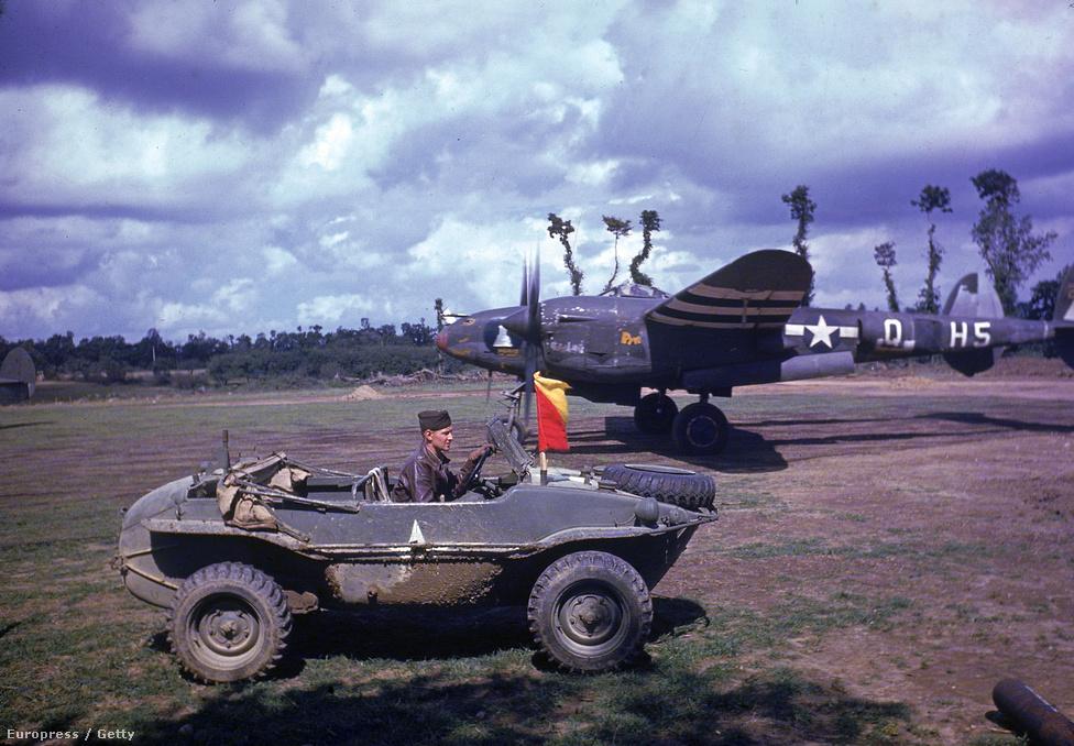 """Felszállásra készül egy  Lockheed P–38 Lightning típusú repülőgép, amelyik a második világháború elején kifejlesztett legnehezebb együléses amerikai vadászrepülő volt. A jármű a """"villám"""" becenevet a brit Királyi Légierő pilótáitól kapta, a németek villás farkú ördögnek, a magyar pilóták pedig létrának nevezték. Közben egy másik pilóta egy foglyul ejtett német járművel épp megérkezik a reptérre. A kép nem sokkal Párizs augusztus 25-i felszabadítása után készült."""