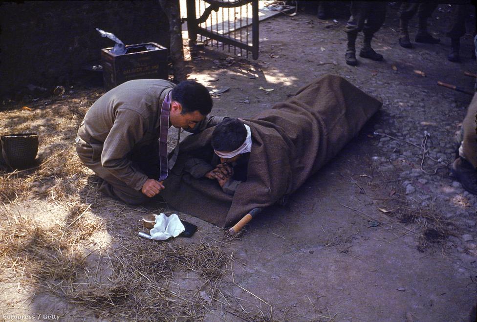 Egy tábori lelkész súlyosan sérült katona  mellett térdel, hogy feladja az utolsó kenetet – valahol Normandiában, 1944 augusztusában.